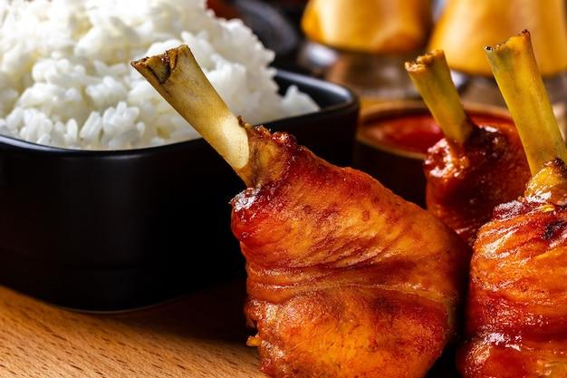 Pernas de frango frito em um prato de madeira com um prato de arroz cozido
