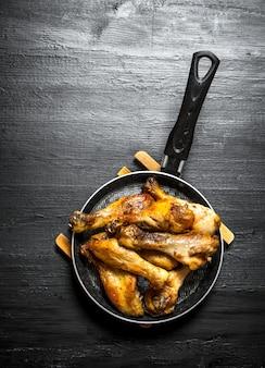 Pernas de frango frito em uma frigideira em um fundo preto de madeira