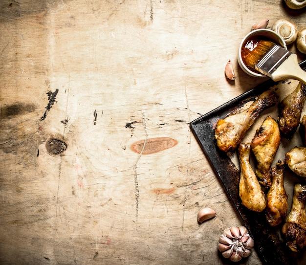 Pernas de frango frito em uma panela com cogumelos, alho e molho picante