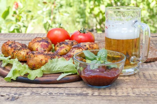 Pernas de frango grelhadas e folhas de alface em uma tábua de cortar de madeira, molho de tomate em uma tigela de vidro decorada com manjericão verde, caneca de cerveja, tomates frescos e pão preto