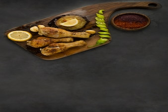 Pernas de frango grelhadas servidas com limão, pimenta e molhos