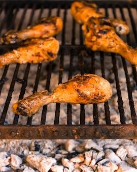 Pernas de frango grelhado brilhante na grelha quente