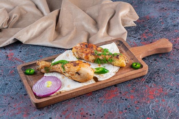 Pernas de frango grelhado caseiro em uma tábua de madeira