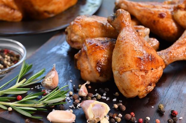 Pernas de frango grelhado com ingrediente em uma tábua de madeira na cozinha
