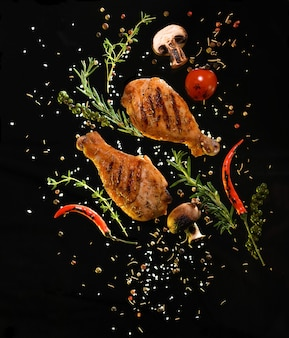 Pernas de frango grelhado com ingredientes em fundo preto
