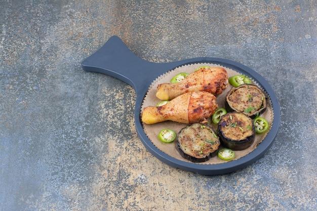 Pernas de frango grelhado com legumes fritos no quadro escuro. foto de alta qualidade