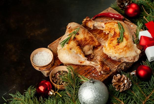 Pernas de frango grelhado de natal com especiarias e ervas, com árvores de natal e brinquedos, porteiros em um fundo de pedra.
