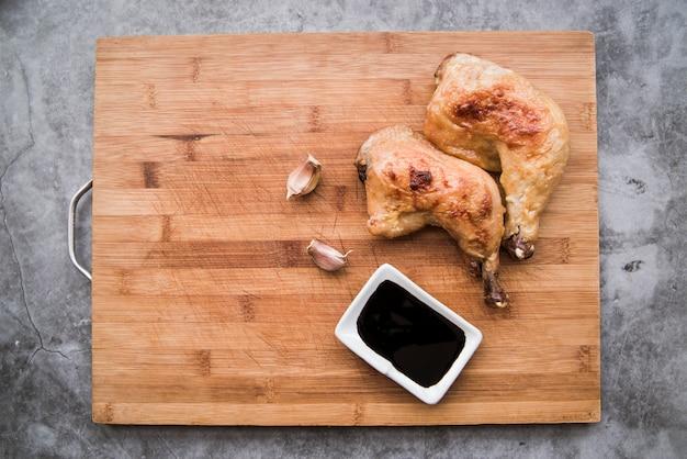 Pernas de frango grelhado delicioso com molho de soja e alho na placa de corte