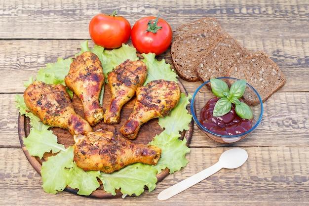 Pernas de frango grelhado e folhas de alface em uma tábua de cortar de madeira, molho de tomate em uma tigela de vidro decorada com manjericão verde, tomates frescos e pão preto com sementes de girassol