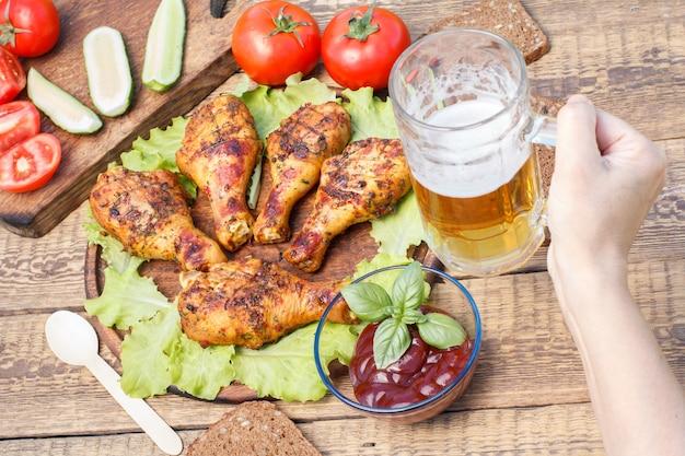 Pernas de frango grelhado e folhas de alface na tábua de cortar de madeira, molho de tomate em uma tigela de vidro decorada com manjericão verde, mão feminina segurando uma caneca de cerveja de vidro, tomates frescos e pepinos cortados