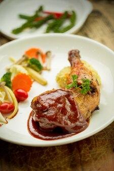 Pernas de frango grelhado e legumes em prato branco isolado na chapa branca