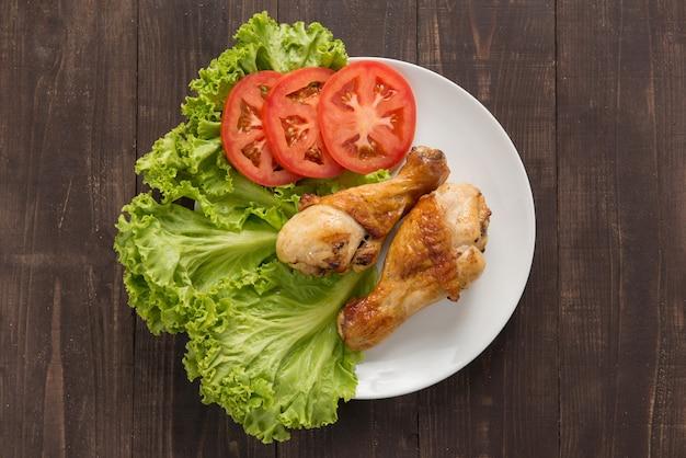 Pernas de frango grelhado e legumes na madeira