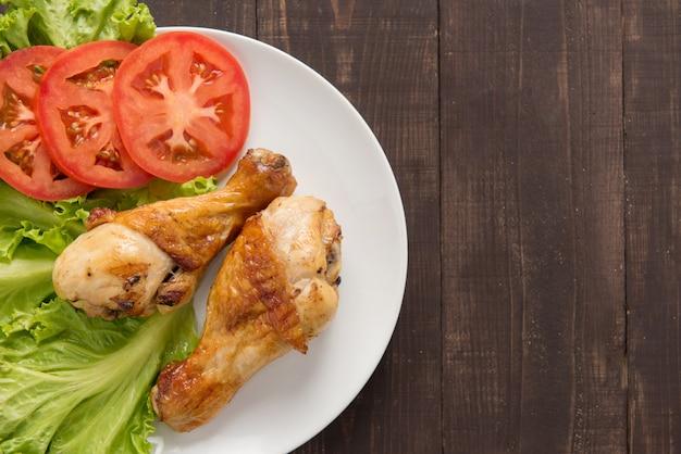 Pernas de frango grelhado e legumes na mesa de madeira.