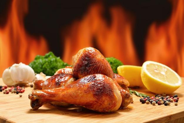 Pernas de frango grelhado e vários legumes em uma lenha