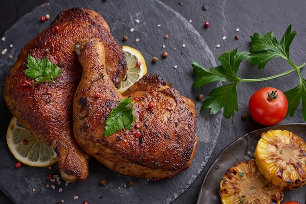 Pernas de frango grelhado em molho barbecue com sementes de pimenta salsa, sal em uma placa de pedra preta sobre uma mesa de pedra preta.