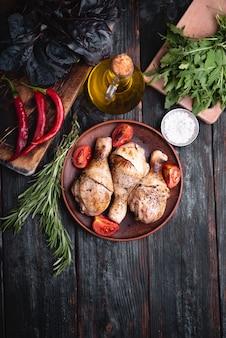 Pernas de frango grelhado, mentira em um prato, ervas aromáticas e temperos para carne