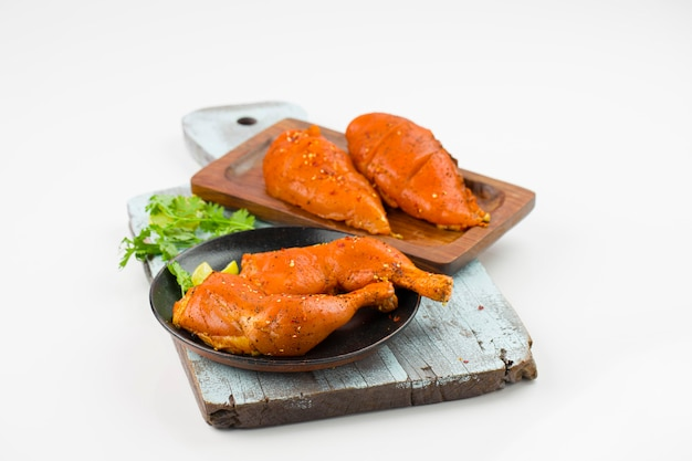 Pernas de frango marinadas e filé de peito que são colocados em uma tábua de corte pintada