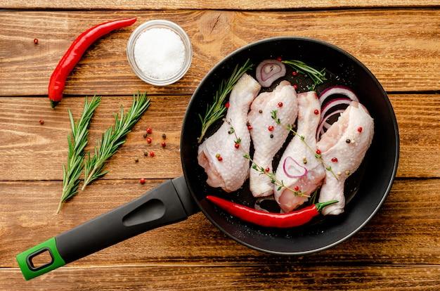 Pernas de frango marinado cru ou coxinhas de frango com temperos e ervas em uma frigideira pronta para cozinhar. conceito de comida mediterrânea. vista do topo