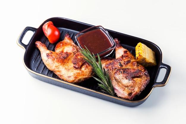 Pernas de frango para churrasco no prato com molho na superfície branca.