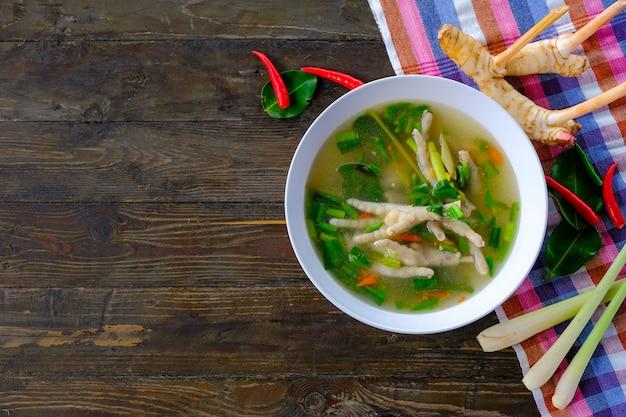 Pernas de frango picante sopa em copo branco na mesa de madeira