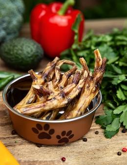 Pernas de frango secas na vasilha de cachorro entre a vegetação na placa de madeira e alguns vegetais no fundo. guloseimas de mastigação para cães domésticos.