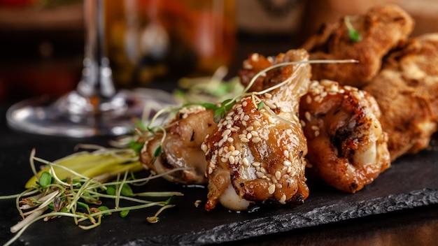 Pernas de frango vidradas e asas de frango, empanadas.