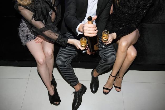 Pernas de garotas glamorosas com taças de champanhe e jovem de terno segurando uma garrafa enquanto estão sentados juntos no sofá