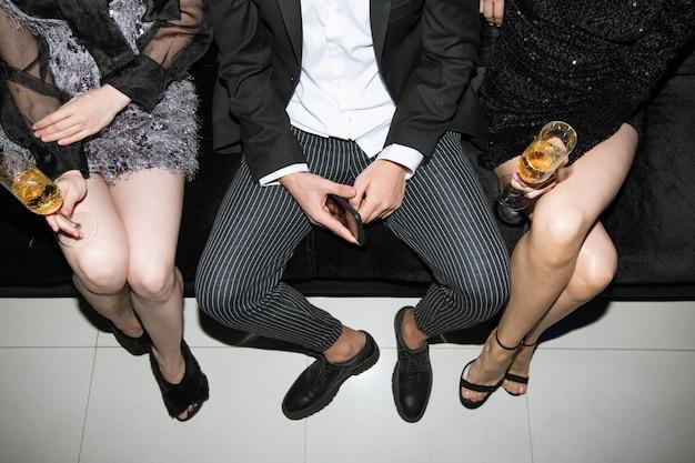 Pernas de garotas glamorosas com taças de champanhe e um jovem de terno sentado no sofá em uma festa em uma boate
