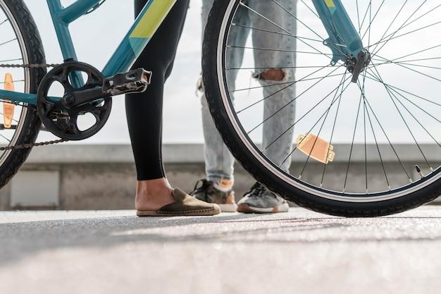 Pernas de homem e mulher ao lado da bicicleta
