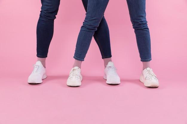 Pernas de homem e mulher em jeans e tênis