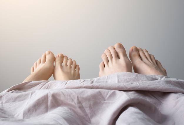 Pernas de homem e mulher na cama. pés de casais na cama, close-up. bom dia.