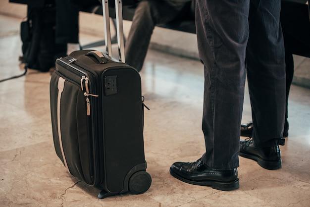 Pernas de homem em pé bagagem no aeroporto