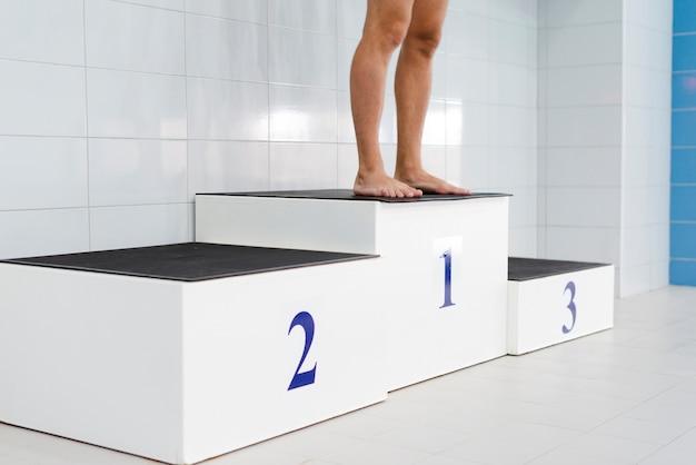 Pernas de homem em pé no pódio da primeira posição