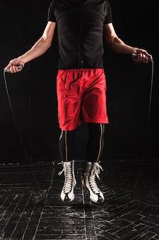Pernas de homem musculoso com pular corda, treinamento de kickboxing no preto