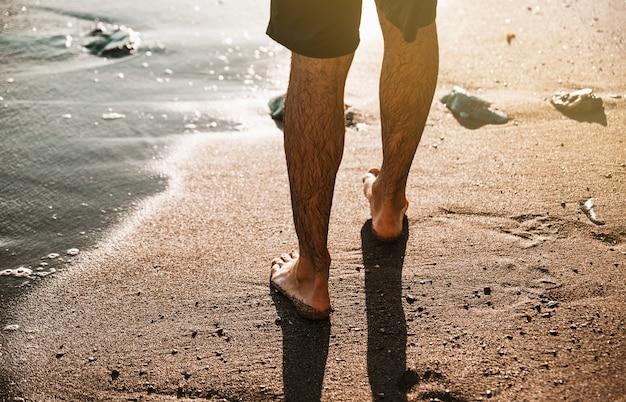 Pernas de homem na costa de areia perto da água