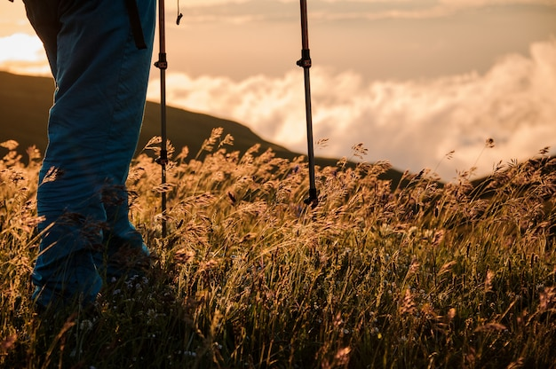 Pernas de homem parado na colina com bastões de caminhadas, olhando o pôr do sol