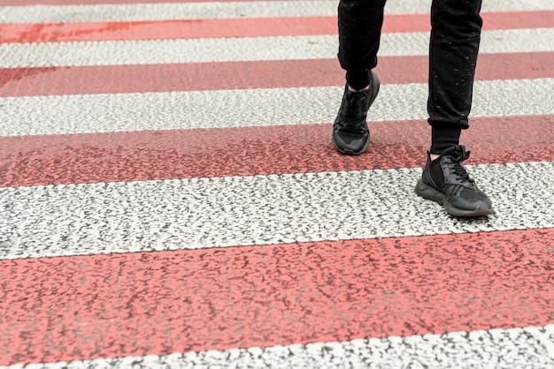 Pernas de homens close-up, passando uma faixa de pedestres