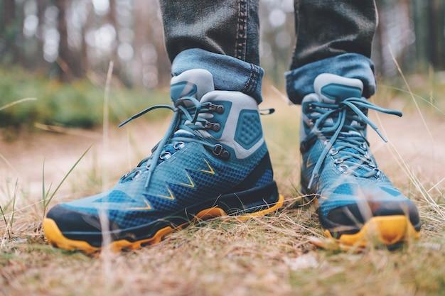 Pernas de homens em botas de trekking para pé de atividade ao ar livre na natureza.