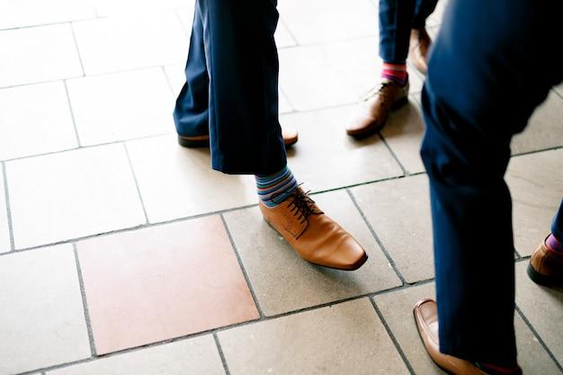 Pernas de homens em calças azuis, sapatos de couro e meias coloridas listradas