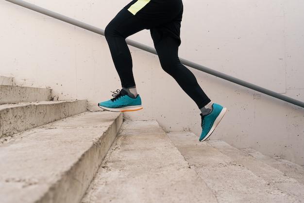 Pernas de jovem a fazer exercícios intervalados nas escadas