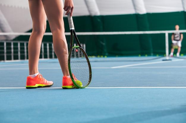 Pernas de jovem em uma quadra de tênis fechada com bola e raquete