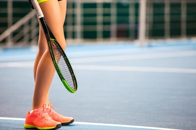 Pernas de jovem em uma quadra de tênis fechada com raquete