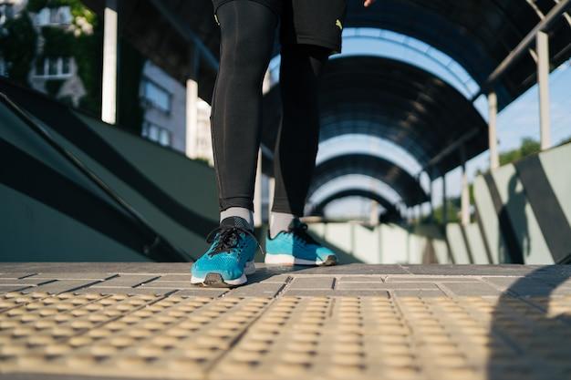 Pernas de jovem praticando exercícios de intervalo nas escadas