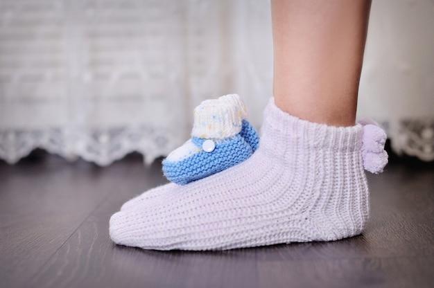 Pernas de mãe grávida e sapatinhos de bebê de malha. Foto Premium