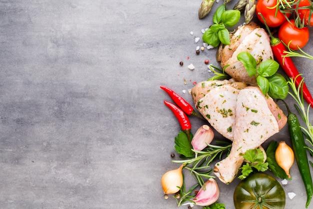 Pernas de marinada de frango, legumes frescos em um fundo cinza. vista superior.