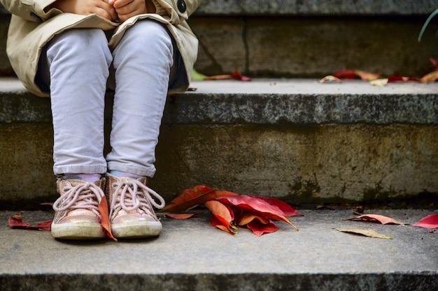 Pernas de menina em sapatos estilo que sentado na escada em patk com folhas caídas vermelhas