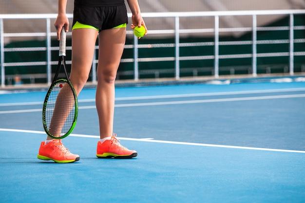 Pernas de menina em uma quadra de tênis fechada com bola e raquete