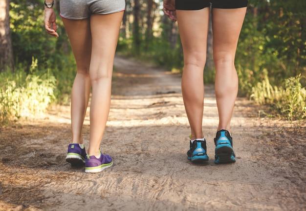 Pernas de menina jovem fitness na trilha da floresta ao pôr do sol