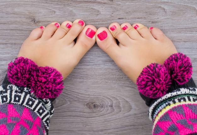 Pernas de meninas com pedicure rosa