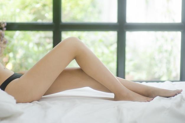 Pernas de mulher asiática sexy na cama branca